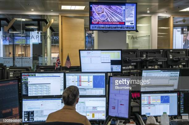 Television screen displays a news report on world stock markets trading lower as a trader monitors financial data on computer screens on the trading...