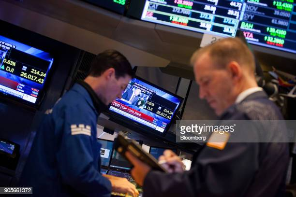 A television screen displays news about the Dow Jones Industrial Average reaching 26000 while traders work on the floor of the New York Stock...