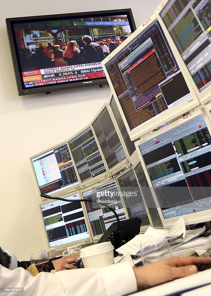 A television screen displays news of Cypriot banks re-opening as a trader monitors financial data on his computer screens at at Shore Capital Group Ltd. brokerage in London, U.K., on Thursday, March 28, 2013. Cyprus's banks opened for the first time in almost two weeks, with new rules curbing access to cash preventing an initial panic to withdraw deposits. Photographer: Chris Ratcliffe/Bloomberg via Getty Images