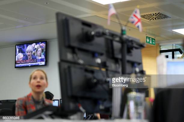 A television screen displays UK Prime Minister Theresa May speaking in the House of Commons as a broker monitors financial data on computer screens...