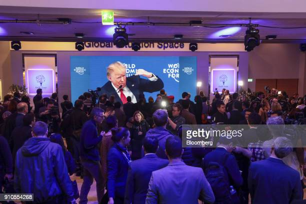 A television screen displays US President Donald Trump delivering a speech during a special address on the closing day of the World Economic Forum in...