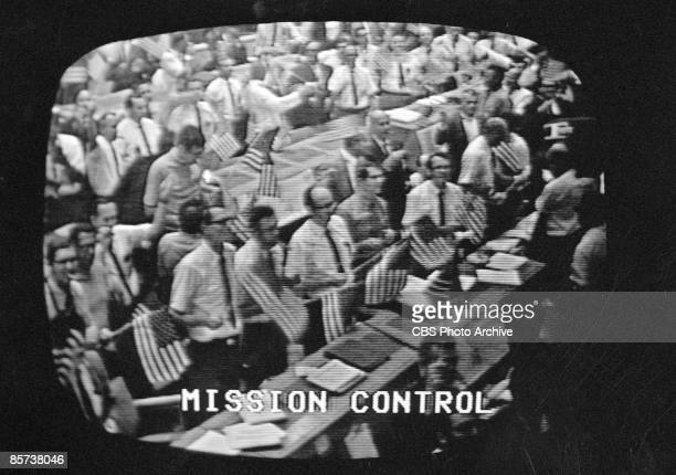 A television screen grab shows the members of mission control waving flags and celebrating the splashdown and return of the crew of the Apollo 11...