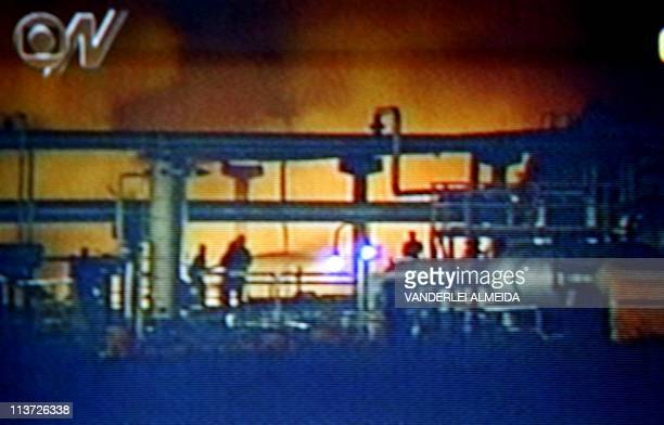 Television screen grab taken 21 April 2003 of an oil refinary in flames while firefighters attempt to extinguish the fire in Aracaju Brazil Imagen de...