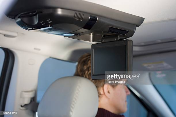 Television screen in car with man driving