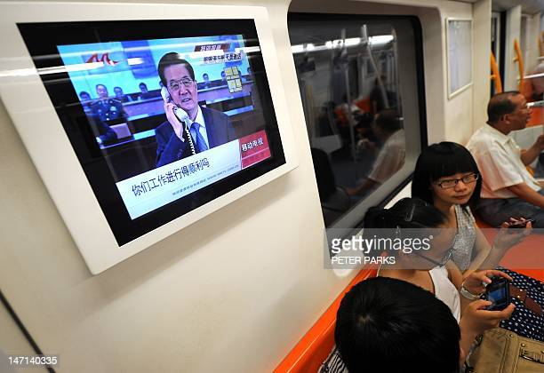 A television screen on a subway train in Shanghai shows Chinese President Hu Jintao speaking by telephone to the three Chinese astronauts aboard the...