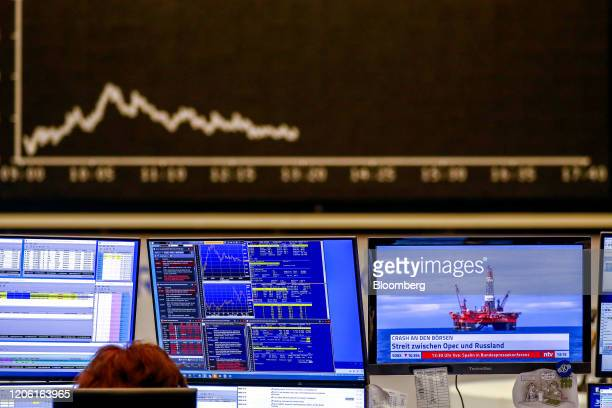 Television screen shows a news report on the breakup of the OPEC+ alliance near the DAX Index curve inside the Frankfurt Stock Exchange, operated by...
