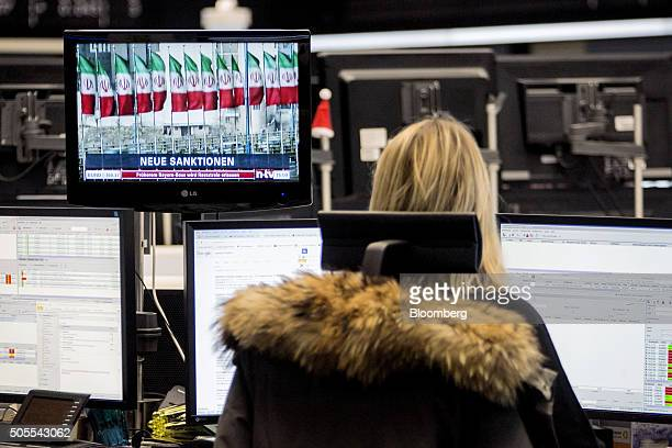 A television screen shows a news report on the lifting of Iran's sanctions as a financial trader monitors data inside the Frankfurt Stock Exchange in...