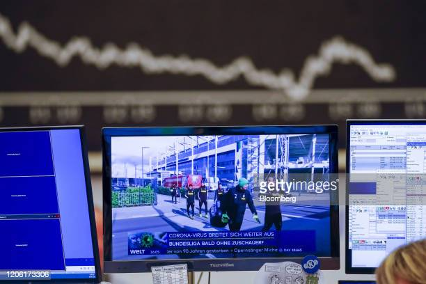 Television screen shows a news report on the potential impact of coronavirus on Bundesliga soccer match attendance inside the Frankfurt Stock...