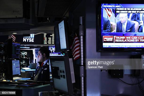 A television screen shows President Donald Trump as traders work on the floor of the New York Stock Exchange on the first day of trading after Donald...