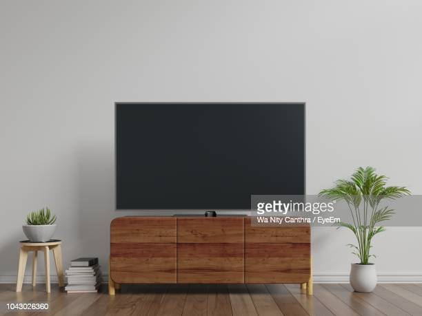 television set on cabinet against white wall at home - televisor - fotografias e filmes do acervo