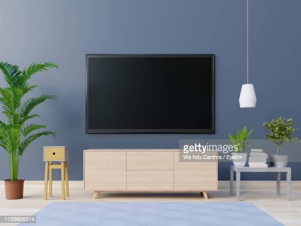 television set with table and potted plants against wall at home - flat screen stock pictures, royalty-free photos & images