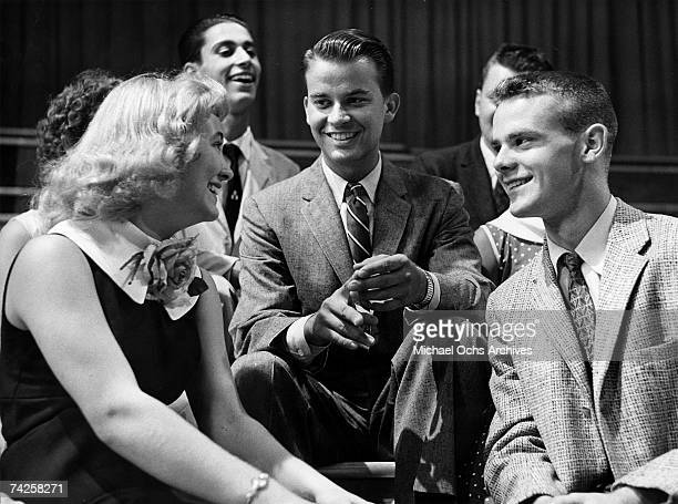 "Television show host Dick Clark poses for a portrait with some kids that are on the set of his show ""American Bandstand"" in circa 1957."