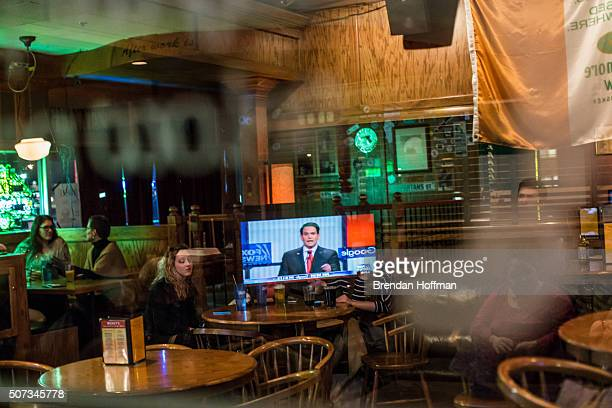 A television showing Republican presidential candidate is reflected in a window at Mickey's Irish Pub during the GOP presidential debate on January...