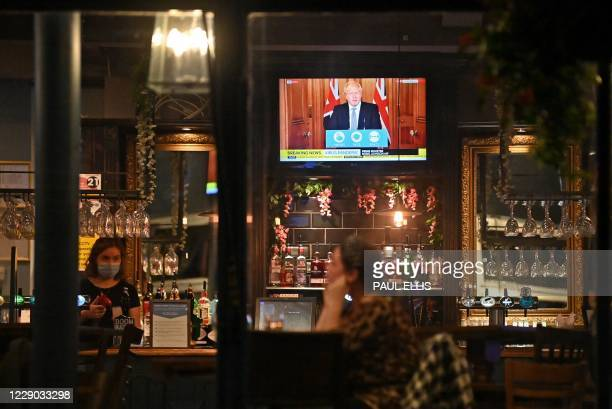 Television shows Britain's Prime Minister Boris Johnson speaking from 10 Downing Street in London, as customers sit at the bar inside the William...