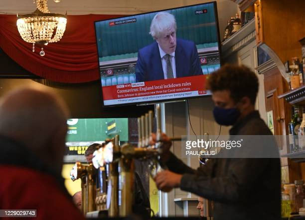 Television shows Britain's Prime Minister Boris Johnson speaking in the House of Commons in London, as customers sit atthe bar inside the Richmond...