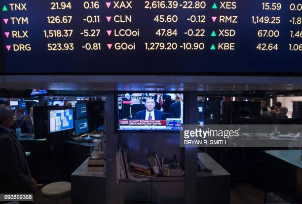 A television shows former FBI Director James Comey testifying before the Senate on the floor of the New York Stock Exchange at the closing bell of...