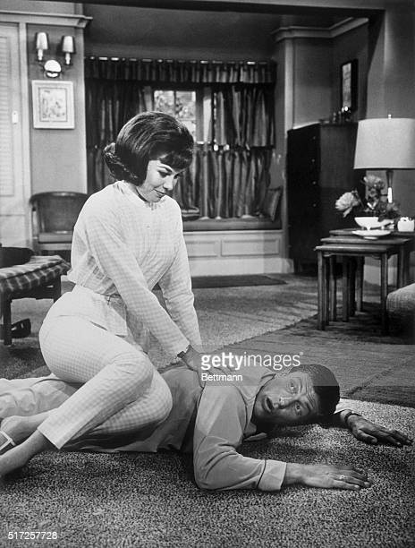 """Television still of Mary Tyler Moore Sitting on Dick Van Dyke's back, as he lies on the floor. From """"The Dick Van Dyke Show"""" . Undated photograph."""