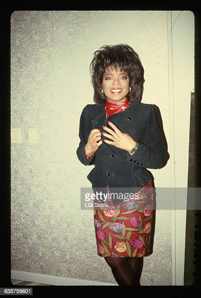 1989 Television talk show host Oprah Winfrey smiles while standing against a wall wearing a navy blue jacket over a flowerpatterned dress
