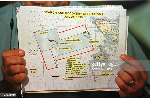 A television technician holds up the official handout map of the search and rescue area off Martha's Vineyard MA before a press conference 21 July...