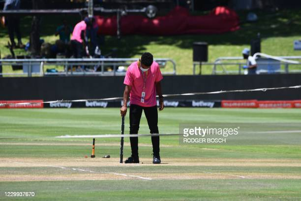 Television technician removes a sensor from the pitch at Newlands stadium in Cape Town, South Africa, on December 4, 2020. - The first one-day...