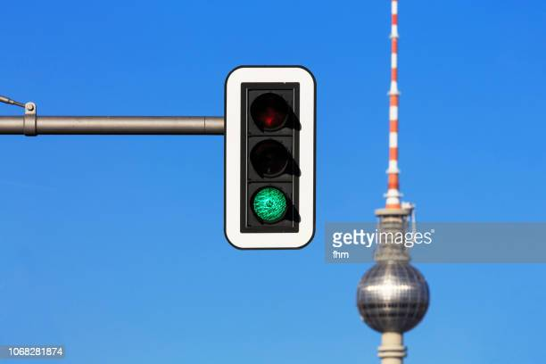 television tower berlin with green traffic light (germany) - road signal stock-fotos und bilder