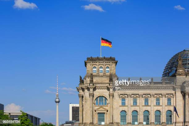 Television towwer and tower of the Reichstag building with german flag (german parliament building) - Berlin, Germany