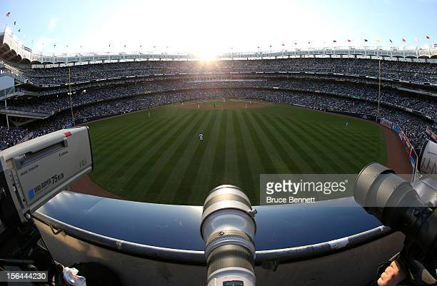 Television video and still camera lenses are seen in centerfield as the sun sets behind home plate while the New York Yankees host the Detroit Tigers...