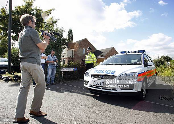 A television video journalist films the front of a police car at the entrance to the private road of the McCann family home in the village of Rothley...