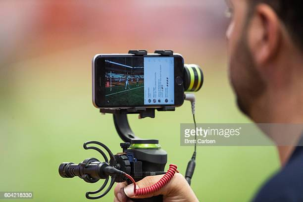 A television video person uses an iphone and stabilizer to film for facebook live broadcast before the game between the Syracuse Orange and the...