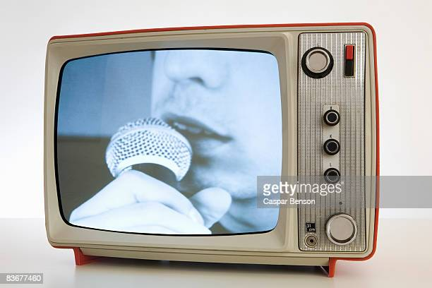 A television with a black and white image of a person singing into a microphone
