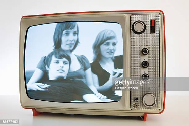 A television with a black and white image of three young people