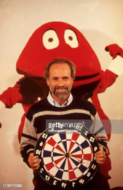 Television writer Antonio Ricci holding a dartboard in his hands The Gabibbo behind him Cologno Monzese Italy 1996