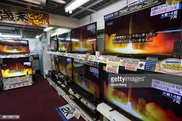 Televisions being sold at an Onoden Co electronics store display a broadcast of a news report on North Korea's Nov 29 missile launch showing footage...