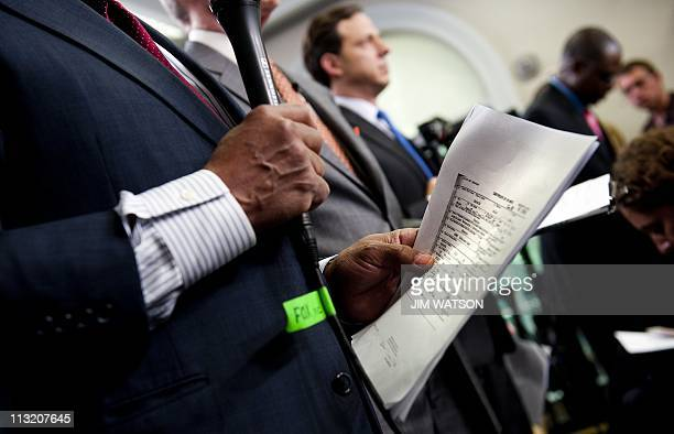 Televison News Correspondents hold copies of US President Barack Obama's longform birth certificate as they prepare for live shots prior to a...