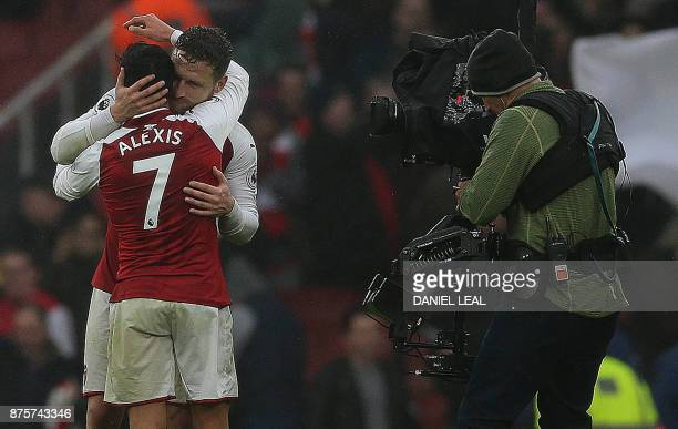 A televsion camnera operator film as Arsenal's German defender Shkodran Mustafi embraces Arsenal's Chilean striker Alexis Sanchez following the...