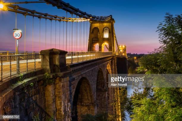 telfords menai suspension bridge over the menai strait at night, anglesey, north wales, uk - menai straits stock pictures, royalty-free photos & images