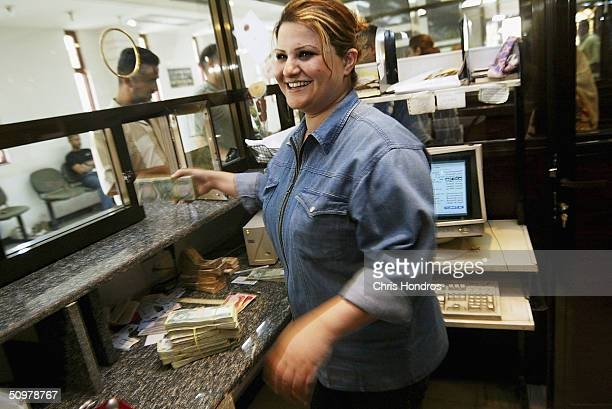 A teller at the Bank of Baghdad in the capital's Karrada neighborhood smiles as she works with money on June 20 2004 in Baghdad Iraq Iraq's banking...