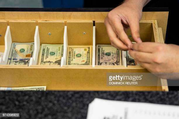 A teller counts cash before New Jersey Gov Phil Murphy arrives on June 14 2018 to place a bet at the Monmouth Park Sports Book on the first day of...