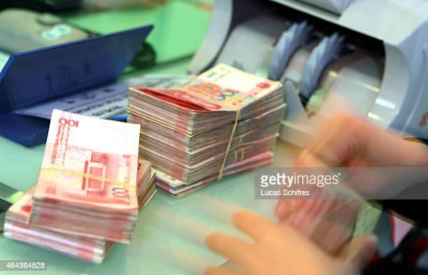 A teller counts Chinese Yuan banknotes at a bank on February 1 2008 in Shanghai China The Chinese Yuan is known locally as the RMB or renminbi which...