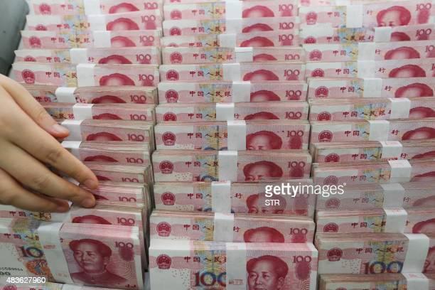 A teller counts yuan banknotes in a bank in Lianyungang east China's Jiangsu province on August 11 2015 China's central bank on August 11 devalued...