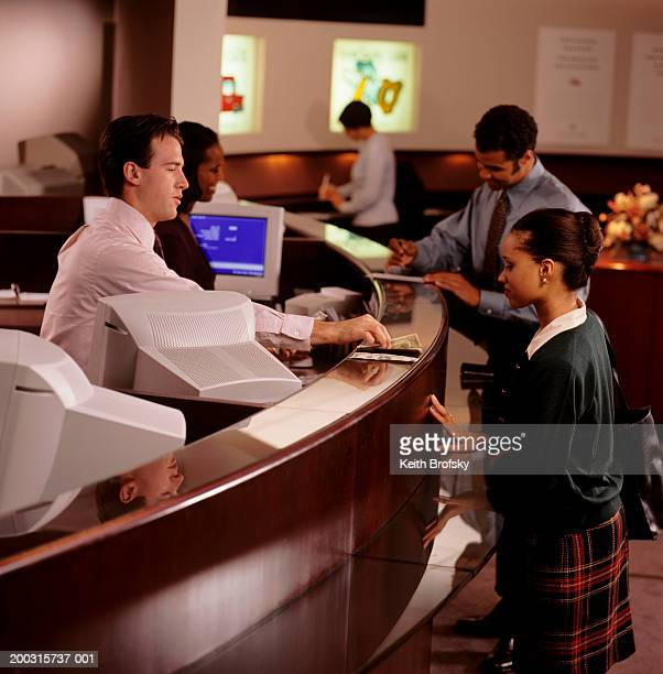 Teller giving money to woman in bank, elevated view