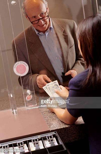 Teller handing money to customer in bank, elevated view