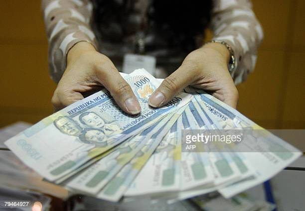 A teller shows thousand peso bills inside a bank at the Makati financial district in Manila 01 February 2008 Philippine monetary authorities trimmed...