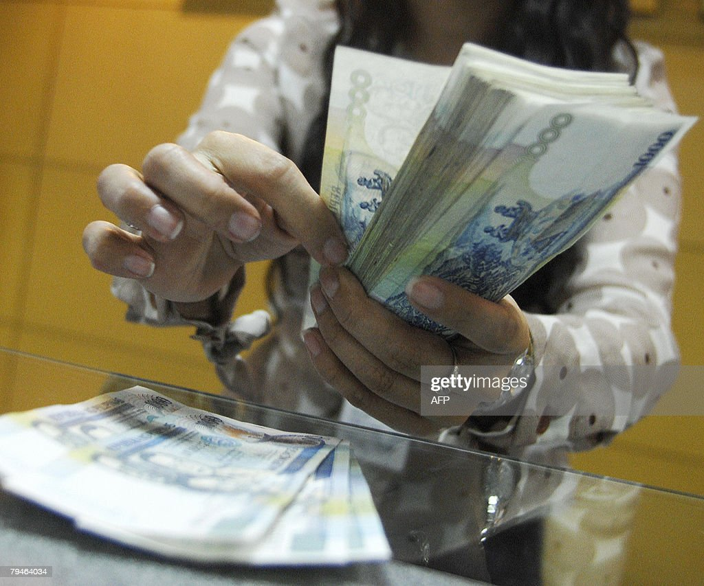 A teller shows thousand peso bills inside a bank at the Makati financial district in Manila, 1 February 2008. Philippine monetary authorities trimmed key interest rates by a quarter percentage point on Thursday, central bank governor Amando Tetangco said. The Monetary Board cut the overnight borrowing rate to 5.0 percent and the overnight lending rate to 7.0 percent, saying inflation was expected to remain within targets for this year and in 2009.
