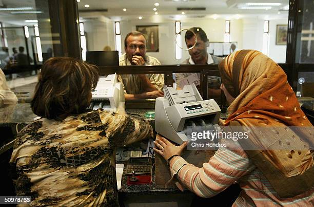 Tellers at the Bank of Baghdad in the capital's Karrada neighborhood work with customers on June 20 2004 in Baghdad Iraq Iraq's banking industry a...