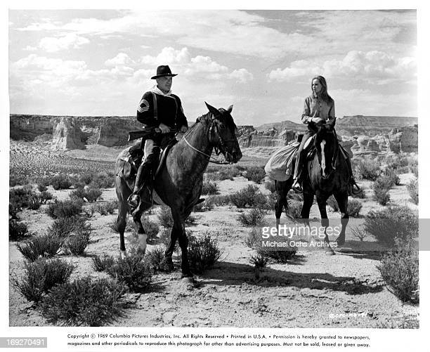 Telly Savalas and Camilla Sparv on horseback in the desert in a scene from the film 'Mackenna's Gold' 1969