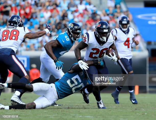 Telvin Smith of the Jacksonville Jaguars attempts to tackle Lamar Miller of the Houston Texans during the game at TIAA Bank Field on October 21 2018...