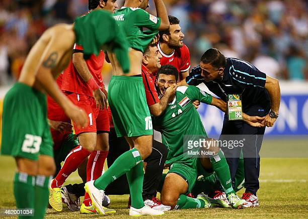 Tem mates rush to Salam Shakir of Iraq after he kicked the winning goal in the penalty goal shoot out during the 2015 Asian Cup match between Iran...