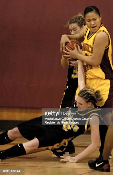 Temecula Valley's Jessie Thompson refuses to let go of the ball as Wilson's Angelica Perez holds on to it during their CIF playoff game in Long...