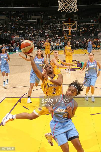 Temeka Johnson of the Los Angeles Sparks goes up for a shot against the defense of Ivory Latta of the Atlanta Dream during their game on September 11...